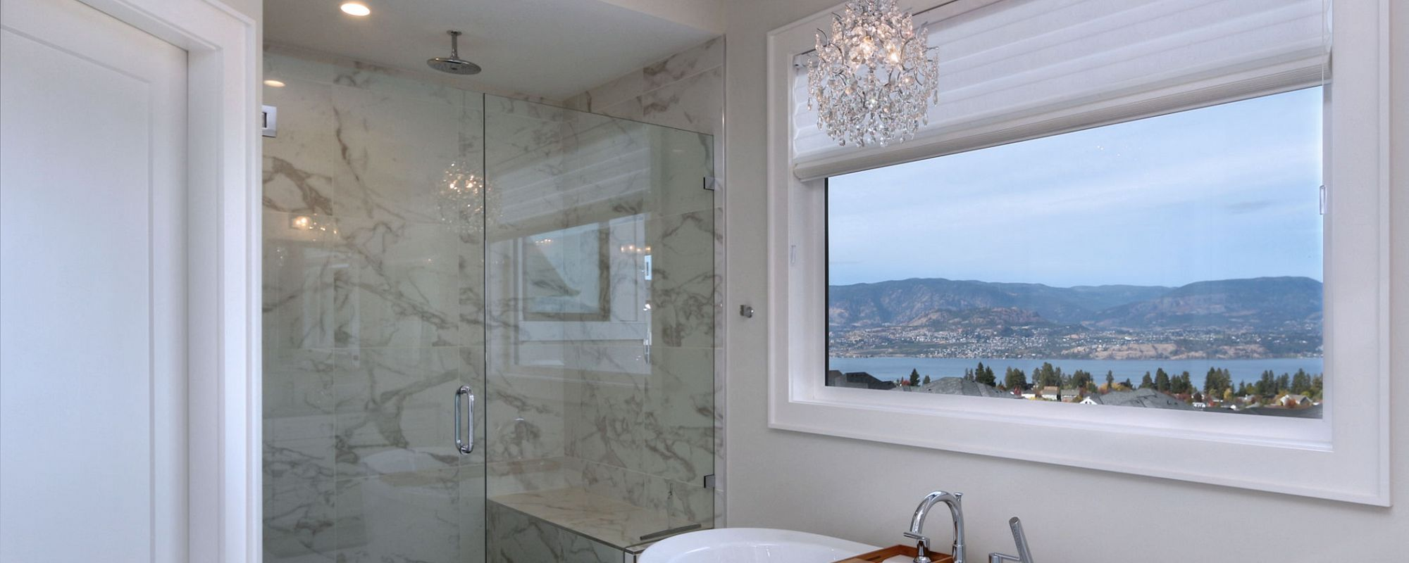 Large bathroom window with chandelier light fixture overlooking the Okanagan valley and lake