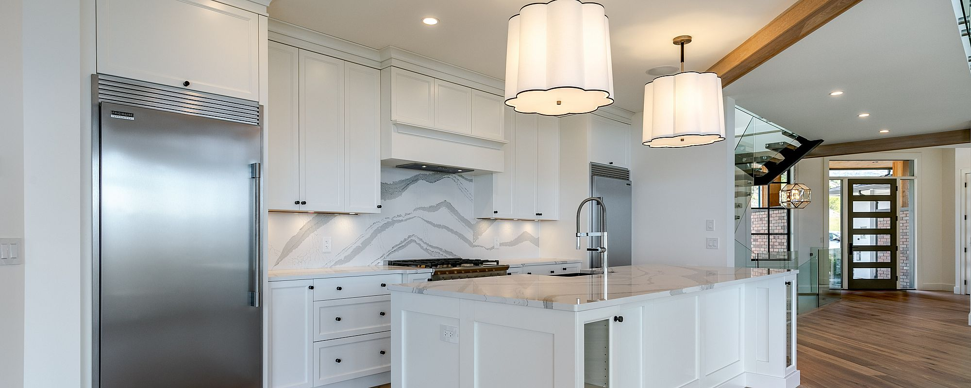 Marble style backsplash in bright kitchen with glass front door in background
