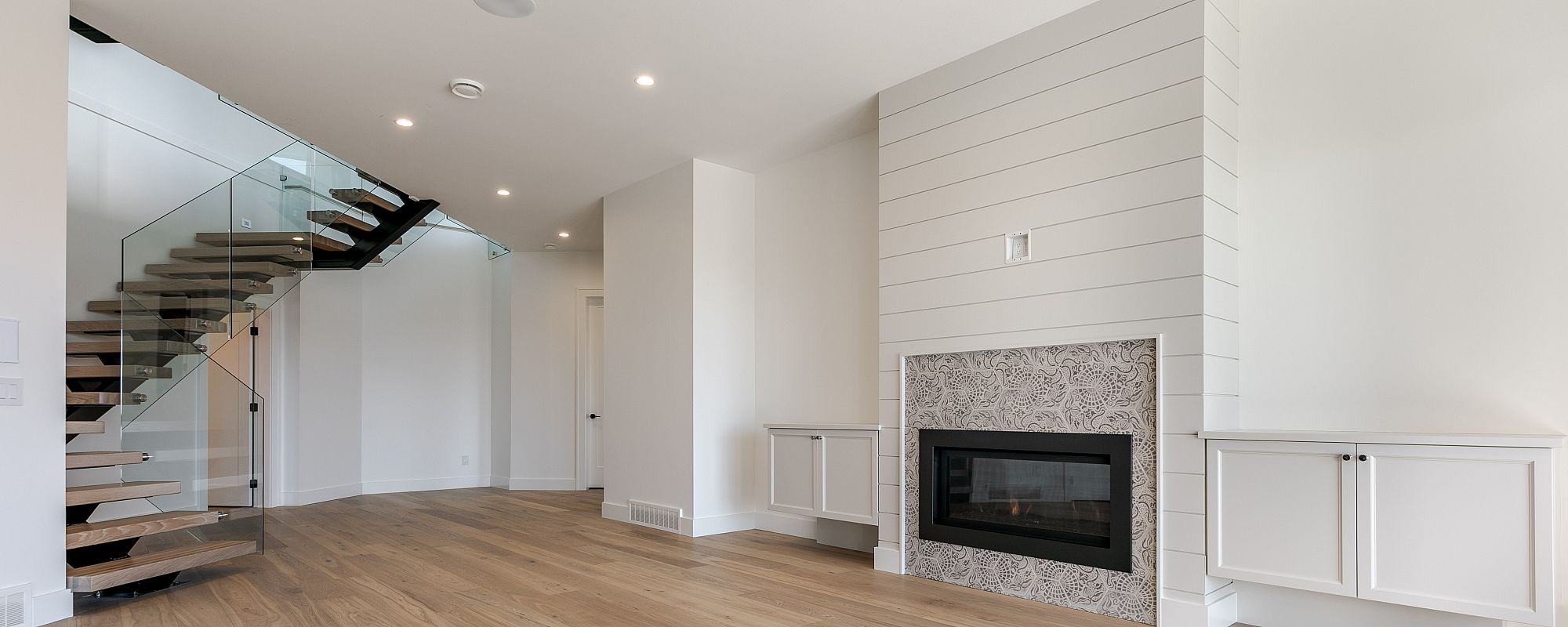 Paisley design fireplace with white framing and wooden steps in custom basement