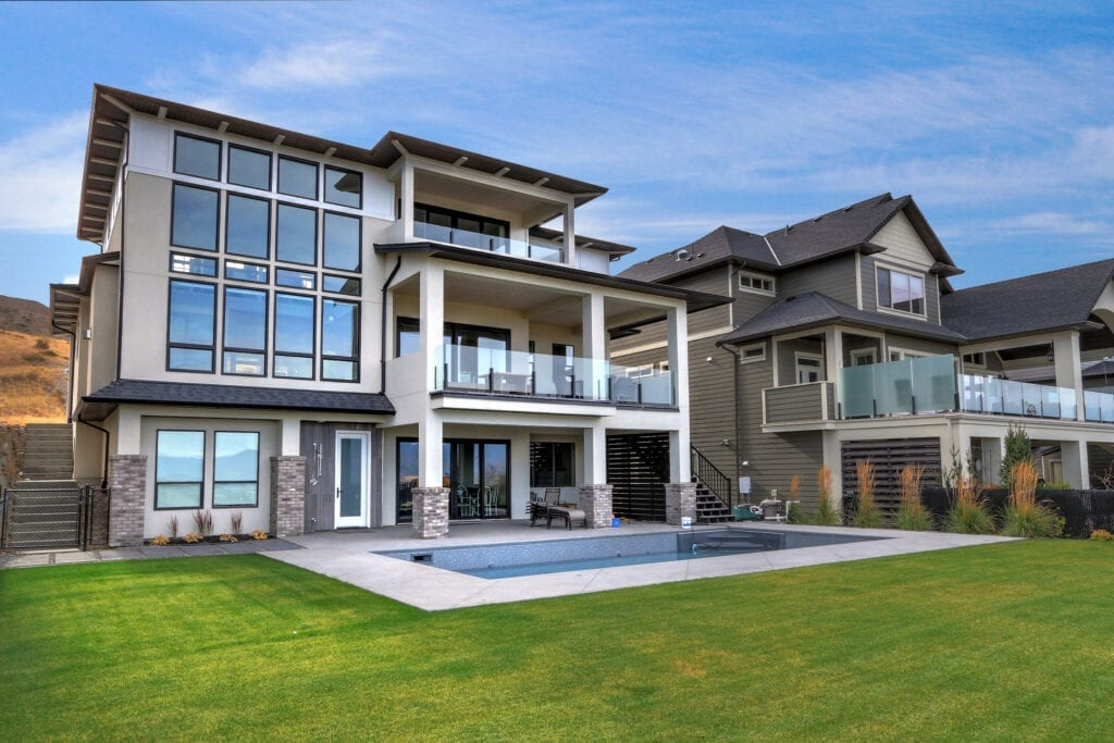 Exterior home design for 470 Rockview Lane with a large in ground pool and windows overlooking the lake