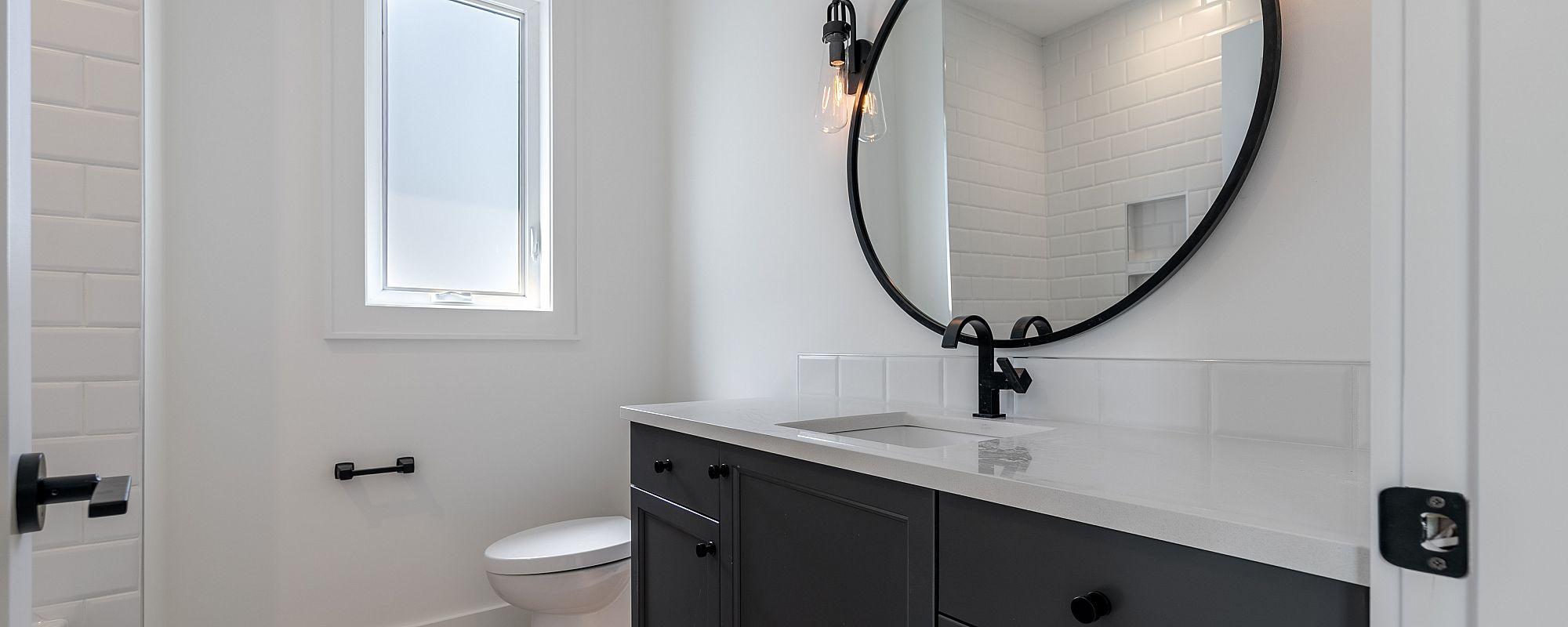 Stark Homes custom bathroom with circular black framed mirror and dark cabinets