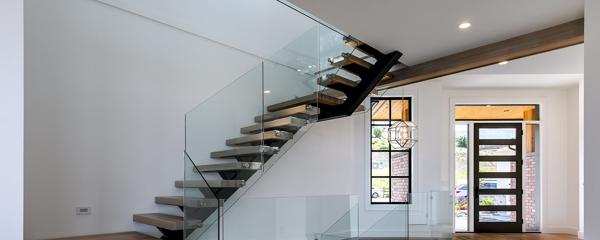 Modern glass and black frame doors and windows in entrance way with wooden stairs