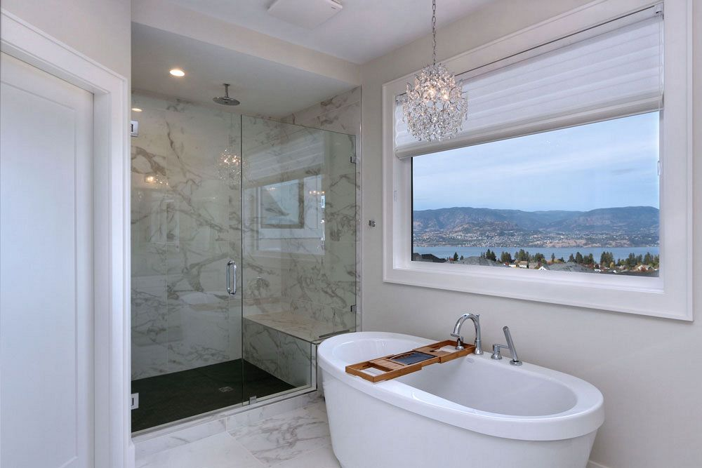 Marble custom bathroom with walk in shower and soaker tub overlooking the Okanagan valley