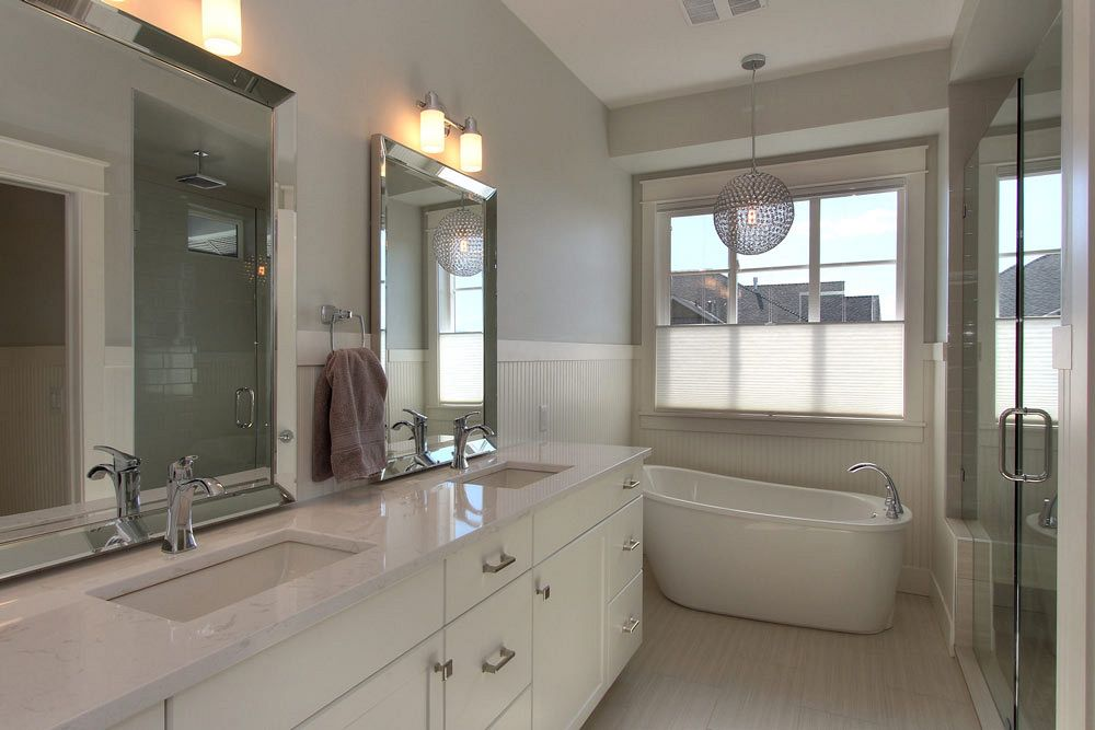 447 Lakepoint Drive custom bathroom with a circular light fixture over a soaker tub, also featuring twin sinks and a large walk in shower at 447 Lakepoint Drive