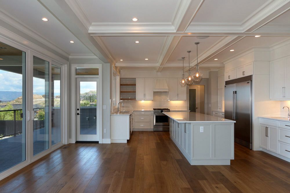 Large open concept kitchen with stainless steel appliances and wooden flooring
