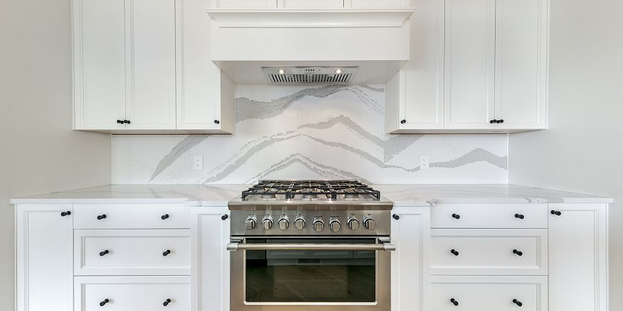 Marble design backsplash in custom kitchen with large gas stovetop and white cabinets
