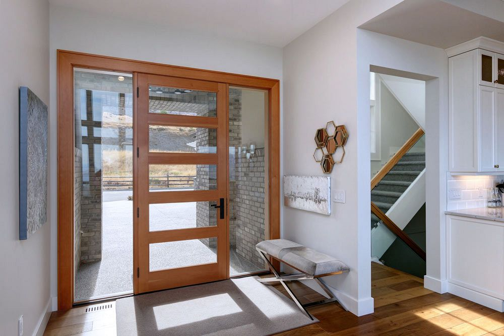 Stark Homes custom home view of the front door with sunlight shining in through glass panels