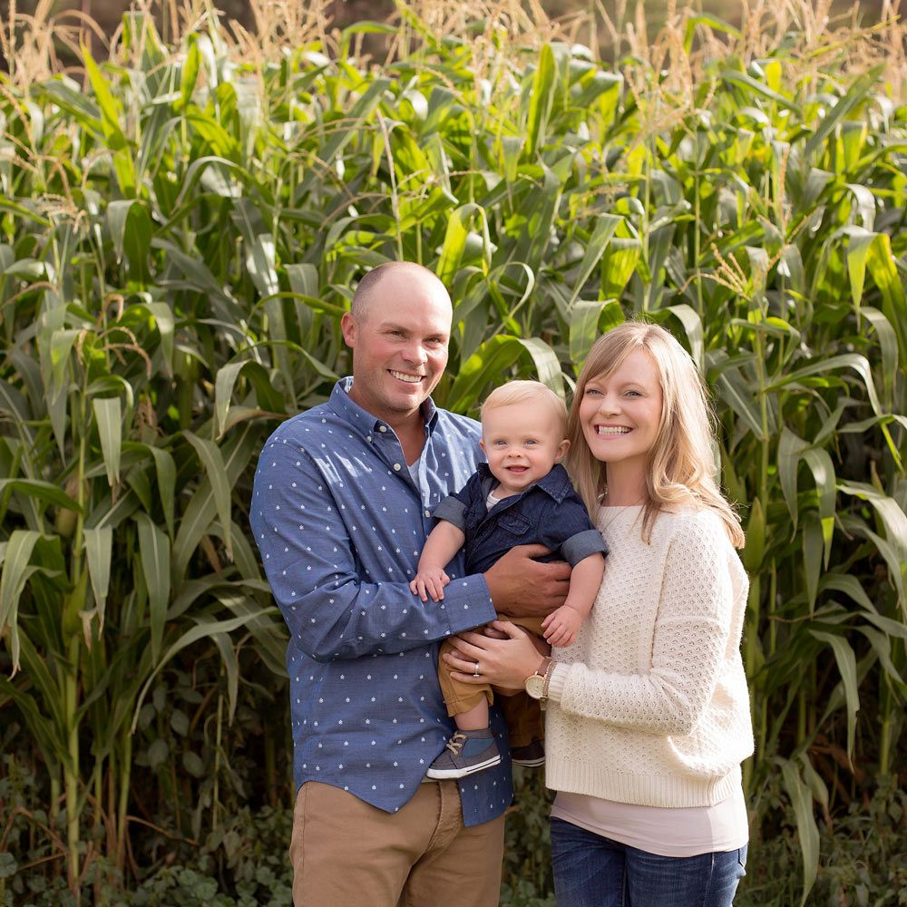 Stark Homes family with Tyler Stark, his wife and their son, standing in front of rows of corn
